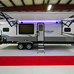 Door Side of the 283RKS with Camp Kitchen Door Open, Awning Extended with LED Lights (Shown in Purple), Optional Solid Steps Extended, Pass- Through Storage Open