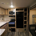 Stainless Steel Microwave, 3- Burner Cook Top with Stove, Matte Black 12V 10 Cubic Foot Refrigerator, Cubie Above Refrigerator, Pantry with 2 Doors Open- Showing 4 Shelves 