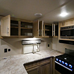 Over-Head Cabinets in Kitchen- Shown Open, Kitchen Sink with Sink Covers, Stainless Steel Faucet, Microwave, 3- Burner Cook Top with Glass Top